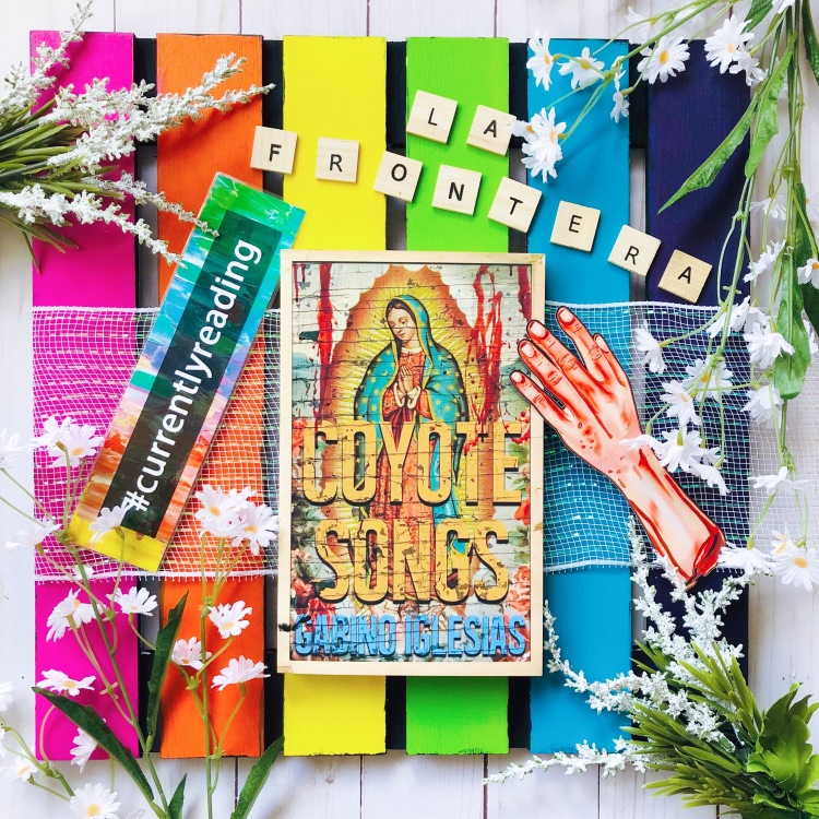 """Coyote Songs by Gabino Iglesias Book Flatlay Photo on Rainbow Board with #CurrentlyReading bookmark and """"La Frontera"""" spelled out in Scrabble Tiles"""