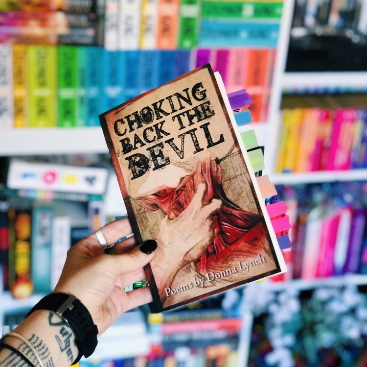 Choking Back the Devil book by Donna Lynch held in front of rainbow bookshelves