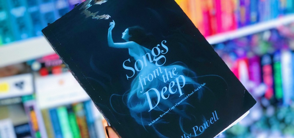 Hand holding the book Songs from the Deep by Kelly Powell in front of a rainbow organized bookshelf