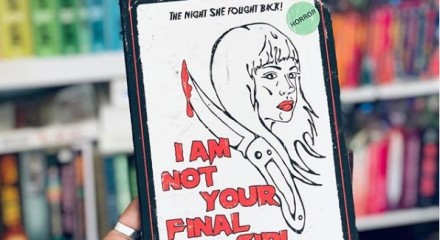"A photo of a hand holding the book ""I Am not Your Final Girl"" in front of a bookshelf with rainbow books"