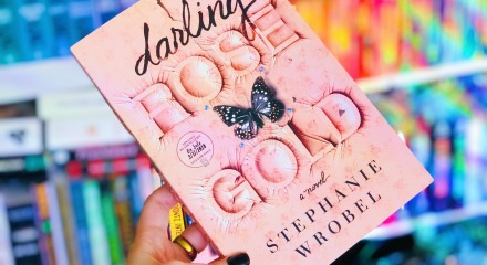 A hand holding the book 'Darling Rose Gold' by Stephanie Wrobel with a pink cover and black butterfly on it, in front of bookshelves with colorful books in rows