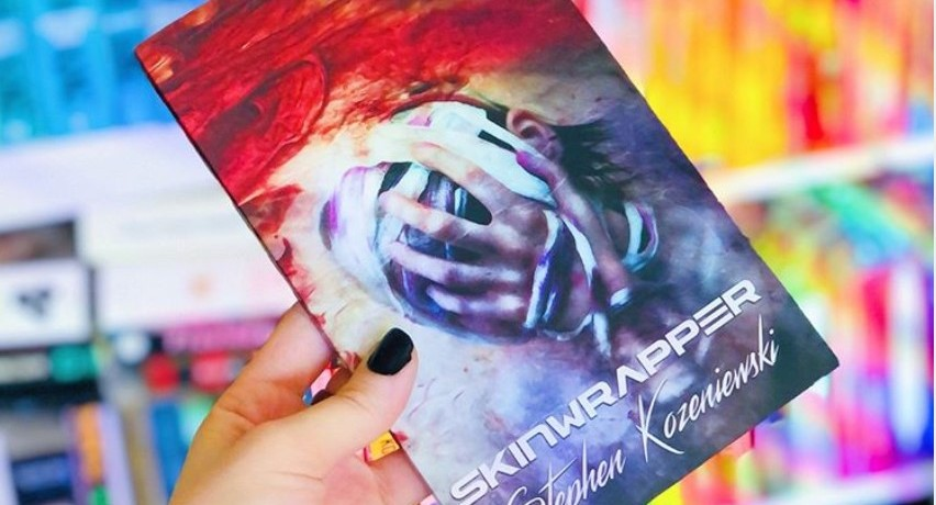 book cover of skinwrappers by stephen kozeniewski, held in a hand in front of a colorful bookshelf